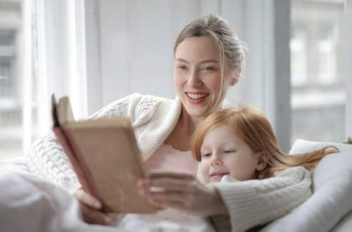 Good moms: Mom reading a book with young daughter.