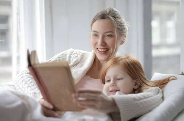 What is a mom? Image of Mom reading a book with young daughter.