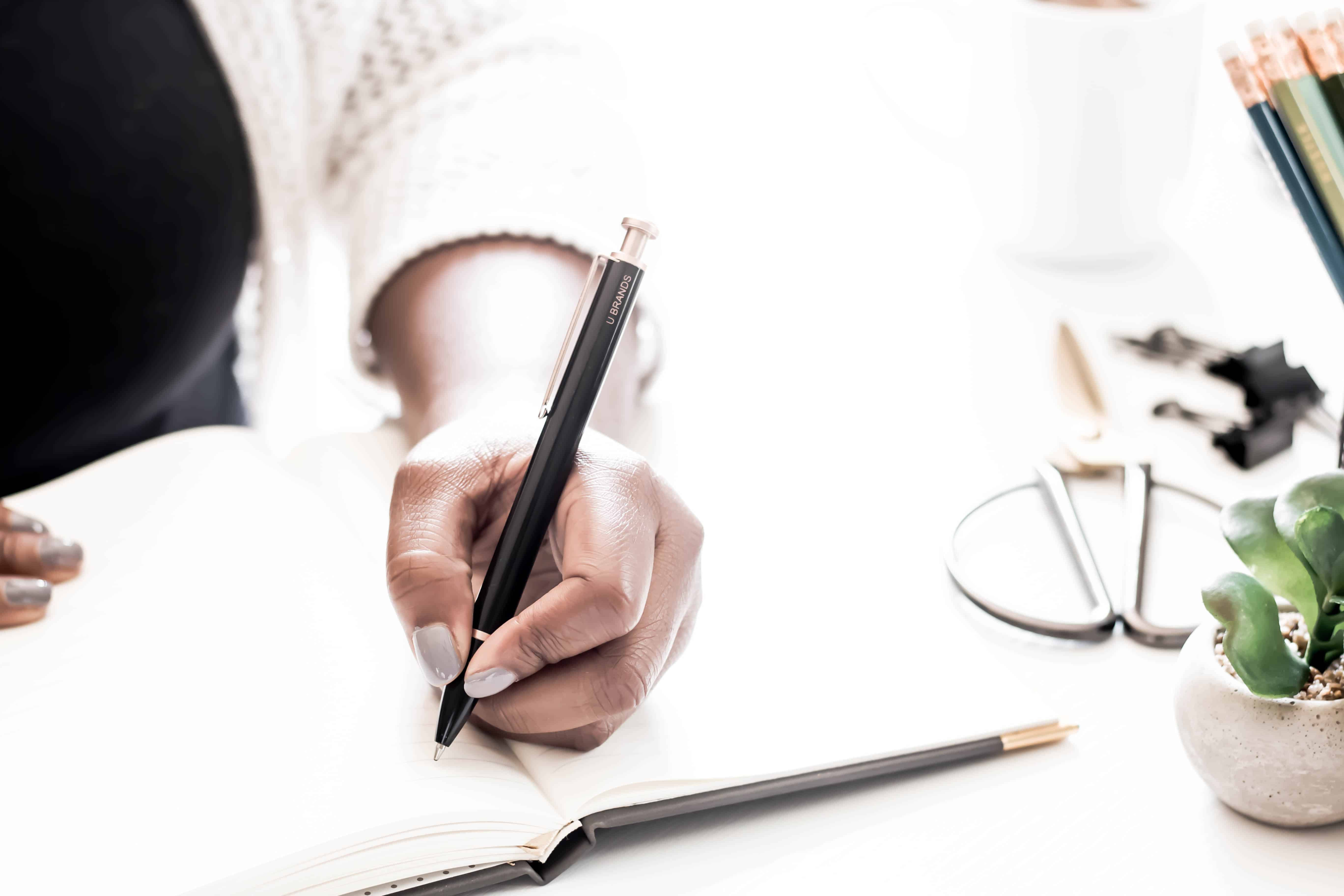 Personal Growth Goals. Woman's arm holding pen writing in notebook