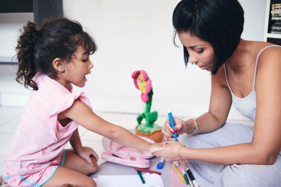 Mother and small daughter doing manicures together