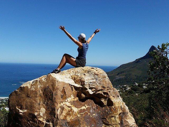 Woman sitting on large rock overlooking ocean